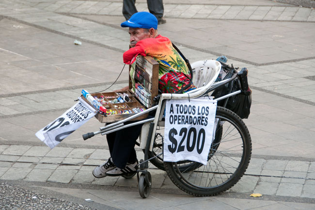 Vendor with homemade wheelchair, Medellín. Street vendors selling cell phone minutes are seen almost everywhere.