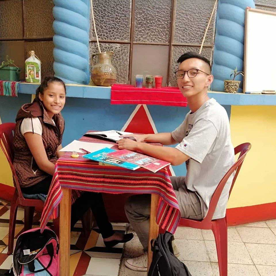 SISAI student (right) tutoring English to student in Educación Para Los Niños program