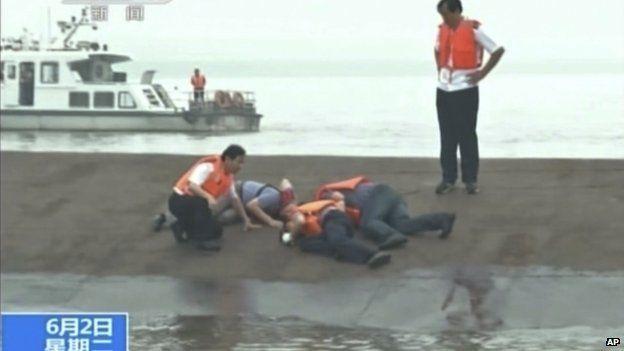 Soccorritori cinesi battono sul fondo del battello capovolto sul fiume Yangtze