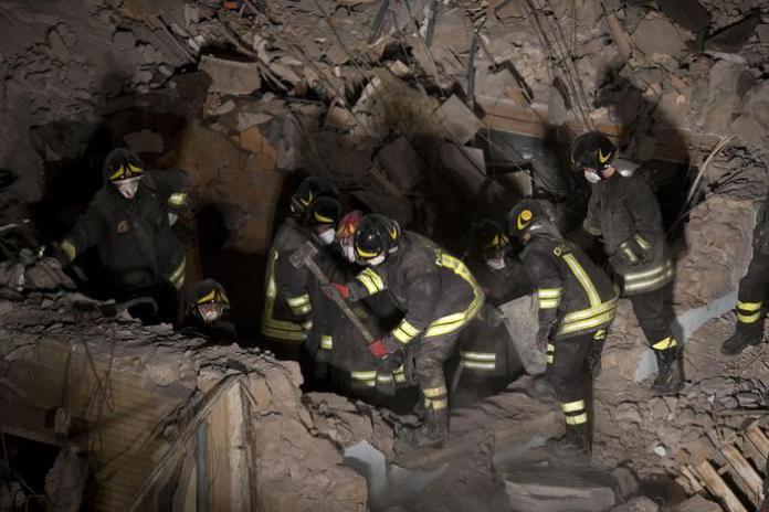 I vigili del fuoco lavorano tra le macerie della palazzina crollata  a Roma