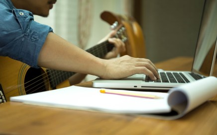 Songwriter with guitar and paper