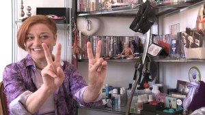 a smiling sex educator making a peace sign gesture with both hands.