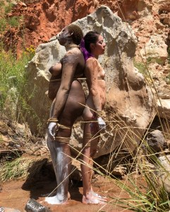 photo of a black woman standing back to back with a smaller asian woman. They have streaks of white paint on their hands and bodies as they stand outside in the desert.