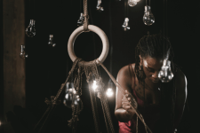 a black woman is looking down, light bulbs are dangling around her and in the center is a ring with ropes
