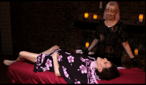 Rowan in a short kimono, laying on a massage table with Barbara Carrella standing next to her, smiling at her.