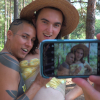 Still image from the short film DIC PIC PICNIK. Two people, one wearing a straw hat, the other topless, pose for a photo, we can see the image in the cell phone as the picture is being taken.