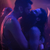 Still image from The Multiverse in a MouthFuck, showing two men in a tight embrace in a nightclub, bathed in purple light.