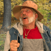 Still image from short film, Pops' Corn showing a smiling man with a grey beard and a fishing hat with trees in the background.