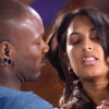 A still from the short film, Wild Card. A close up of stars Bishop Black and Kali Sudhra of them standing close and he appears to be stoking her neck.