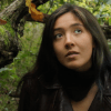 Still image from short film, Forest Affair. A dark haired feminine person looks towards the camera with a tree behind her.