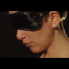 Still image from the experimental short film, Lumilust. A face in profile, wearing a blind fold.