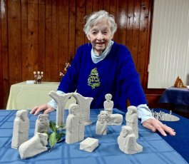 Dorothy Faunce, Exhibit organizer, stands behind one of her 22 nativity scenes she displayed. It is a replica of the hand carved stone designs found throughout much of Ireland.
