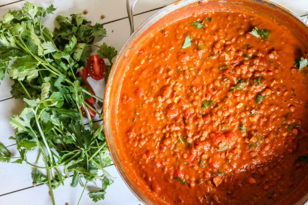 Pan of gluten free, vegan Creamy Coconut Lentil Curry with tomatoes and cilantro