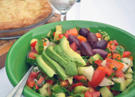 Bowl of chopped salad served with wine and spinach pie.