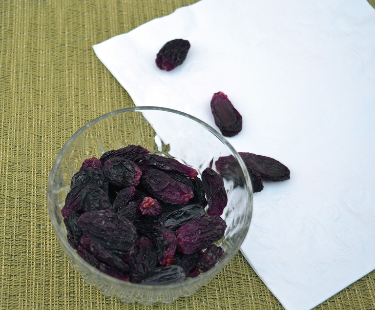 bowl of dehydrated black seedless grapes as raisins