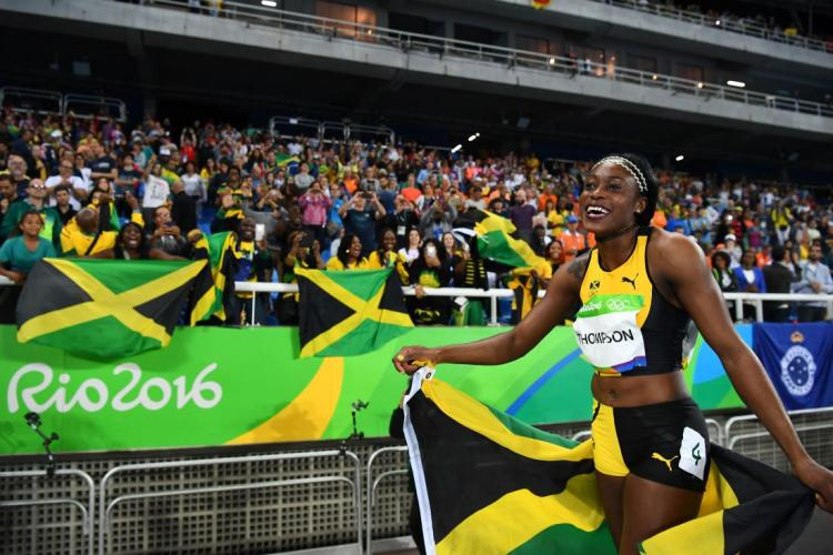 Jamaican track athelete Elaine Thompson celebrates after she won the Women's 100m Final during the athletics event at the Rio 2016 Olympic Games at the Olympic Stadium in Rio de Janeiro on August 13, 2016. / AFP / FRANCK FIFE (Photo credit should read FRANCK FIFE/AFP/Getty Images)