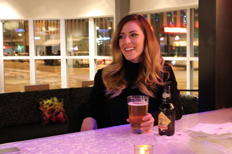 A girl drinking a beer at Aloft hotel in downtown Denver, Colorado