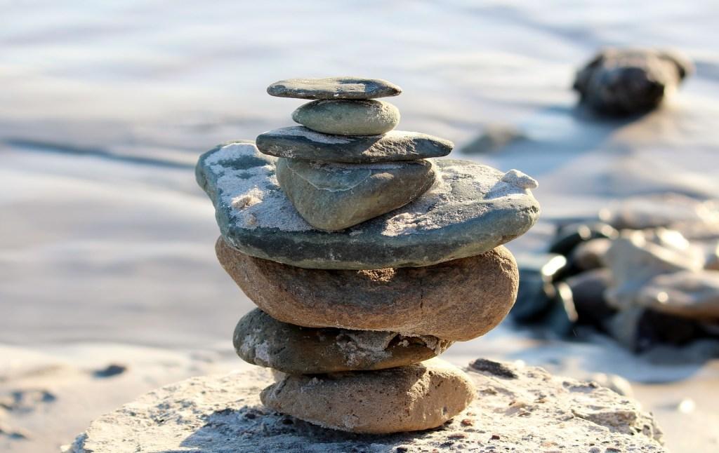 Kuvassa on kiviä pinottuina toistensa päälle ison rantakiven päällä.