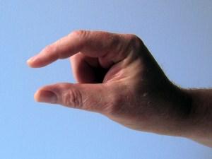 Eine Hand, Daumen und Zeigefinger deuten Kleinheit an