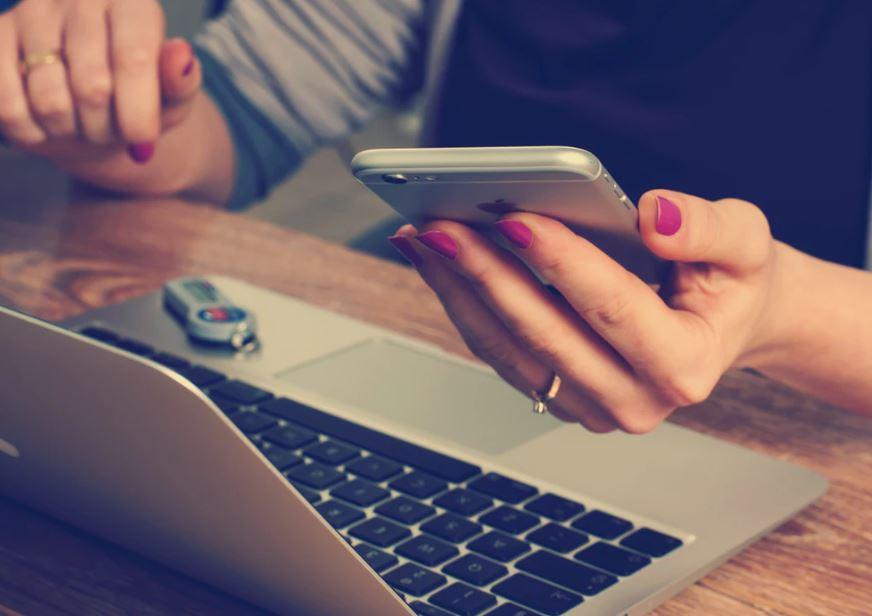 mani con laptop e cellulare che telefonano