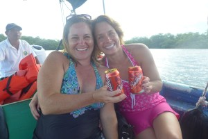 Amy and Crissey smiling on a boat with a beer