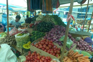 large vegetable stand with tomatoes, carrots, onions etc