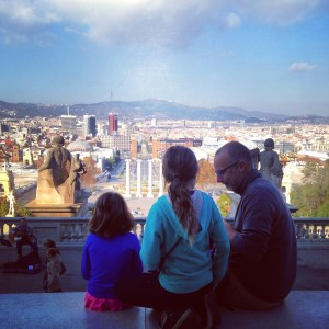 the girls with Jacob sitting in front of a view of Barcelona