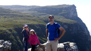 Jacob and the girls stand on top of rocks in front of Fernwood Peak