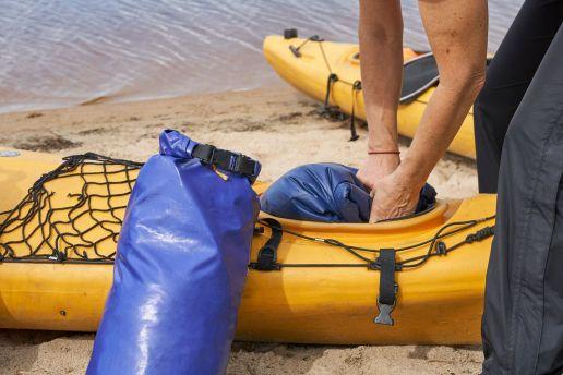 Canva - Female hiker puts a waterproof bag into the kayak