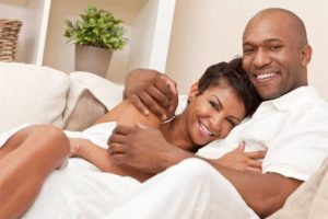 couple with beautiful smiles cuddling in bed