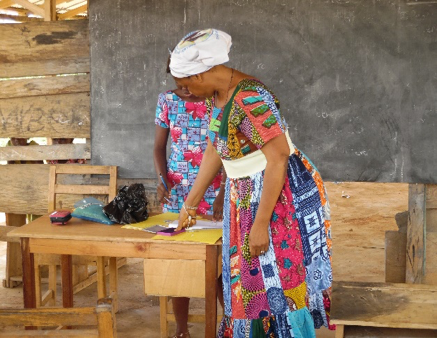 women stands over a table of documents at her microcredit training
