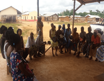 group of women gather in a cirlce for microcredit training