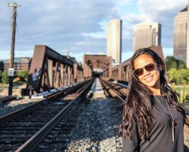 Confident woman on railroad tracks