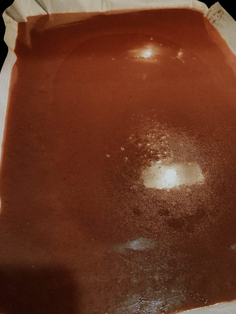 Parchment-lined baking sheet with caramel cooling