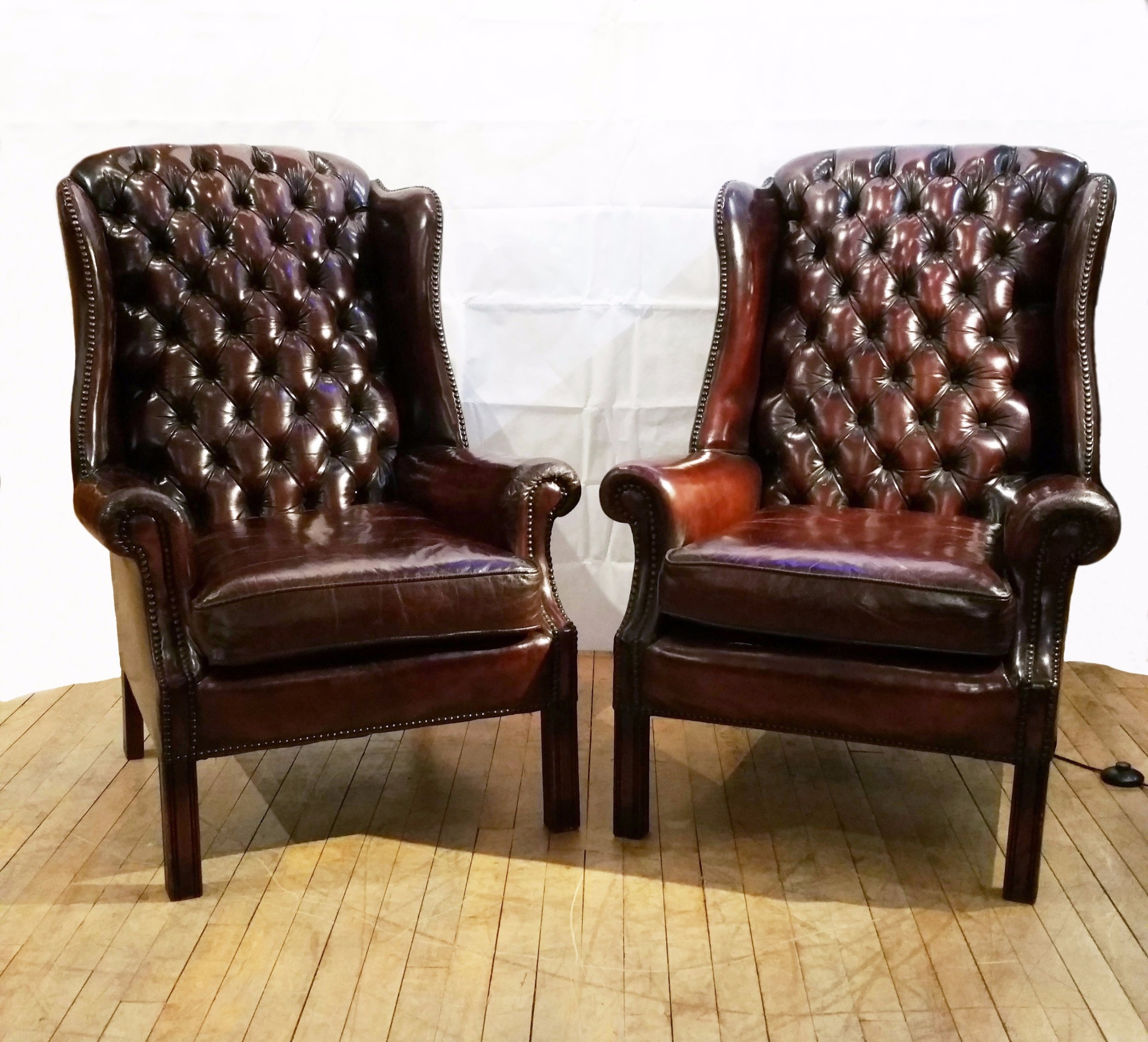 leather wing chairs uk marine captains chair pair of deep buttoned upholstered