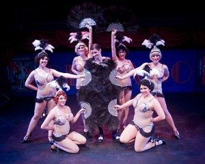 Fan dancers in full regalia, for All He Cares About Is Love. (Clockwise from lower left: Nikki Dizon, Sara Malloy, Julie Rodgers-Baker, Jen Ciombor, Angela DiMarco, Jessica Orozco. Center: Garrett Ard as Billy Flynn. Production Photo courtesy of Ken Beach.)