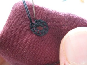 To end, make a small stitch to connect the ring and pass the needle through to the back side of the work..
