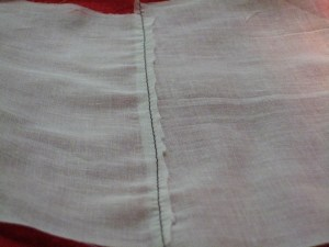 Trim free side of seam allowance down to 1/2 its starting width.  (Seen from back.)