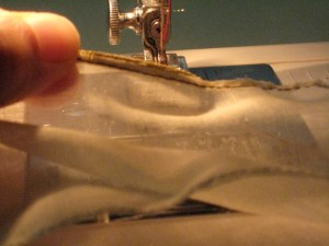 Trim the seam allowance and press the ribbon to the front side of the hem.
