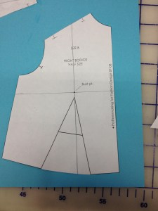 We're going to have to line the two halves of the bodice up accurately after they are split.  Draw in another guideline across the piece.  It should be perpendicular to the center front line, and run through the bust point.  (Hint: on the slopers from our book, you can use the little cross-hairs around the bust point as a guide for this.)