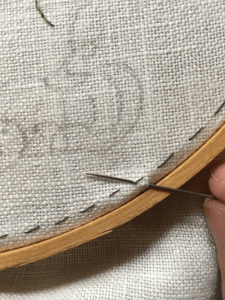 Small stitch into and out of the top side of embroidery, near the edge.