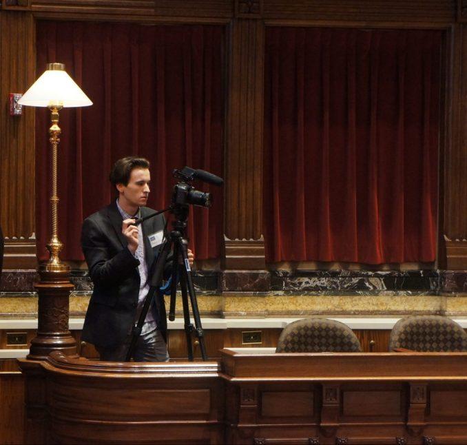 2016 session intern Rob Uniacke operating a camera in the Senate Chamber.