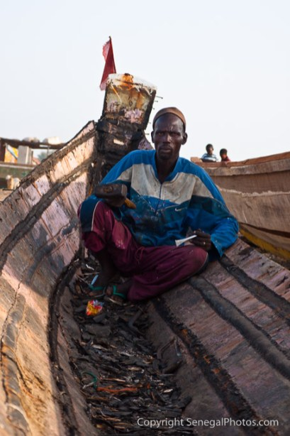 A man repairing an old pirogue in N'Dar Tout quarter of Saint-Louis, Senegal. Photo by Marko Preslenkov.