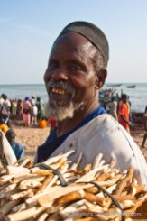 Afternoon life and trading at bustling fish market on the beach in coastal town of Mbur, Senegal. Photo by Marko Preslenkov.