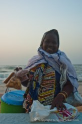 Woman selling home made pastries and peanuts on the beack at Yoff virage, Dakar, Senegal. Photo by Marko Preslenkov.