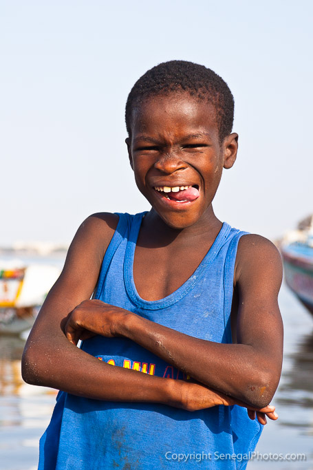 A happy kid posing on the shores of Senegal river in N'Dar Tout quarter of Saint-Louis, Senegal. Photo by Marko Preslenkov.