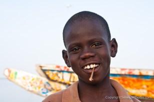 A smiling kid with an eco toothbrush on Senegal river shore in N'Dar Tout quarter of Saint-Louis, Senegal. Photo by Marko Preslenkov.