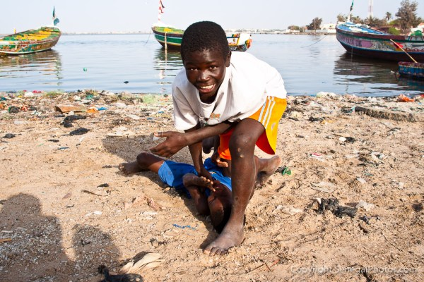 Kids imitating famous Senegalese wrestling fighters and moves on the shores of Senegal river in N'Dar Tout quarter of Saint-Louis, Senegal. Photo by Marko Preslenkov.
