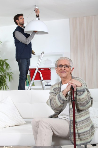 Older lady with electrician fitting a new light