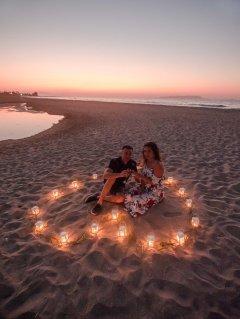 Glückliches verlobtes Paar im Herz aus Kerzen Laternen Windlichter Abend am Strand in Hersonissos Kreta Analipsi Kato Gouves Hochzeitsplanung Planung Dekoration Service